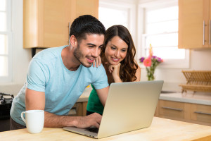 Husband and wife couple sharing a computer laptop social network